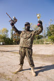 Paintball player with gold cup. Paintball player with gun and gold cup stock photos