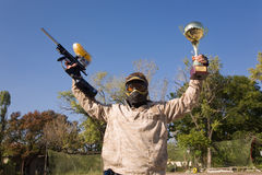 Paintball player with gold cup. Paintball player with gun and gold cup royalty free stock image
