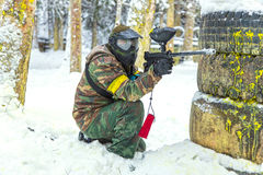 Paintball player with gun behind tires on snow Royalty Free Stock Photography
