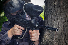 Paintball player. Hidding in the forest Stock Photo