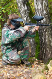 Paintball player is hiding and shooting aside. In the forest Stock Photo