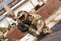 Paintball player hunting. Paintball player in camouflage uniform, outdoors royalty free stock photos
