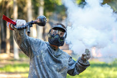 Paintball player with marker and activated smoke grenade Stock Photo