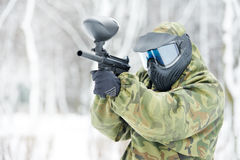 Paintball player with marker at winter outdoors. Paintball extreme sport player wearing protective mask and comouflage clothing with marker gun at winter Royalty Free Stock Image