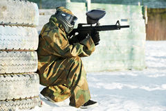 Paintball player with marker at winter outdoors. Paintball extreme sport player wearing protective mask and comouflage clothing with marker gun at winter Stock Photo