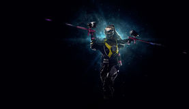 Paintball player is playing the game. Female paintball player is playing the game in the dark Royalty Free Stock Image