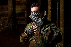 Paintball player preparing for battle. Paintball Sport Player Wearing Protective Mask Aiming Gun And Shotted Down With Paint Splash Royalty Free Stock Photos