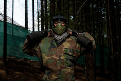 Paintball player preparing for battle. Paintball Sport Player Wearing Protective Mask Aiming Gun And Shotted Down With Paint Splash Royalty Free Stock Photo