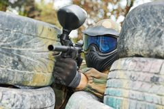 Paintball player. In protective uniform and mask aiming gun before shooting in summer Stock Photography