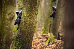 Paintball player in protective uniform and mask aiming gun in th. E forrest cover Royalty Free Stock Images
