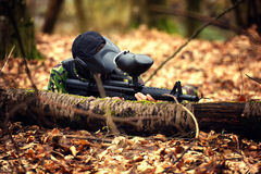 Paintball player in protective uniform and mask aiming gun in th. E forrest cover Stock Image