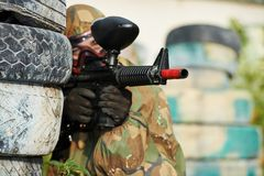 Paintball. Player in protective uniform and mask aiming marker gun in summer Stock Images
