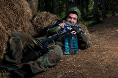 Paintball player resting on the ground Stock Photography