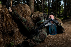 Paintball player resting on the ground Royalty Free Stock Photo