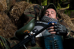 Paintball player resting on the ground Stock Image