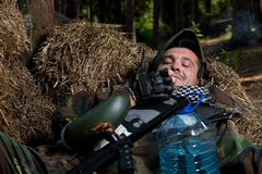 Paintball player resting and smoking a cigar Stock Photos