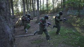 Paintball player running on battle field during shooting game in summer forest. Slow motion. Team players with gun playing in paintball game in adventure park stock footage
