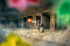 Paintball player shoot. In direction of opposite teams royalty free stock images