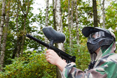 Paintball player shoots aside in forest. Autumn day royalty free stock images