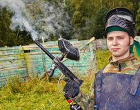 Paintball player shoots out the gun Stock Images