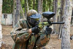 Paintball player. Paintball sport player man in protective camouflage uniform and mask with marker gun outdoors Royalty Free Stock Photos
