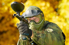 Paintball player. Paintball sport player in protective uniform and mask aiming gun before shooting in summer Stock Photo