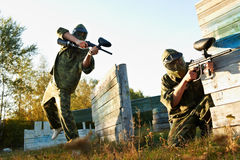 Paintball player under attack. Paintball sport players during tactical training game attack in forest with protective uniform and masks Royalty Free Stock Images