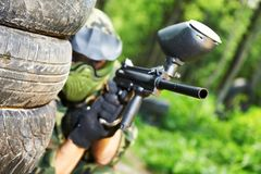 Paintball player under cover Royalty Free Stock Photos