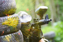 Paintball player under gunfire. Paintball sport player wearing protective mask aiming gun from shelter under gunfire attack with paint splash Royalty Free Stock Images