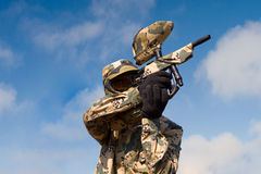 Paintball player in uniform over sky background royalty free stock photography