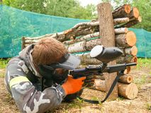 A paintball player who is ready to shoot from hiding. Lying on the ground and shooting royalty free stock images