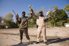 Paintball players with gold cup. Paintball players with gun and gold cup stock photos
