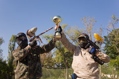 Paintball players with gold cup. Paintball players with guns and gold cup Royalty Free Stock Image