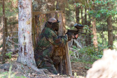 Paintball Players Hide Behind Tree Stock Photo