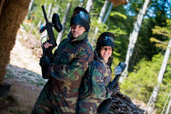 Paintball players posing to the camera. Happy paintball sport players team girls and guys in protective camouflage uniform and mask with marker gun outdoors Stock Photography