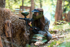 Paintball sniper ready for shooting. Paintball sport player in protective uniform and mask aiming and shooting with gun outdoors stock images