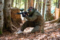 Paintball sniper ready for shooting. Paintball sport player in protective uniform and mask aiming and shooting with gun outdoors stock photos