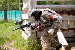 Paintball sport player. Takes cover in shelter Stock Photo