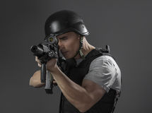 Paintball sport player wearing protective helmet aiming pistol , Royalty Free Stock Images