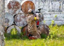 Paintball sportsman in ambush behind rusty barrels Stock Photography