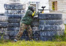 Paintball sportsman standing behind tires and shooting Royalty Free Stock Photography