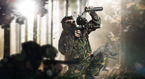 Paintball team in action forest location. Day light Stock Photos