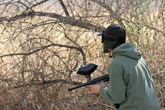 Paintball teen. Paintball - teen with paintball gun and face mask looking out for the enemy Royalty Free Stock Photography