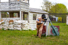 Paintball warrior with paint gun and fortress behind Stock Image