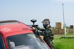 Paintballer, das hinter Auto sich versteckt Lizenzfreie Stockbilder