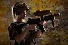 Paintballer de la muchacha con el arma del marcador Fotos de archivo