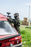 Paintballer hiding behind car. In camouflage cloths Stock Photography