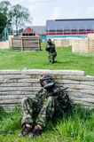 Paintballer hiding behind wall. In camouflage cloths Royalty Free Stock Images