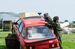 Paintballers che si nasconde dietro l'automobile Immagini Stock Libere da Diritti