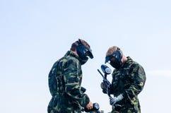 Paintballers que se coloca en campo de batalla Fotografía de archivo